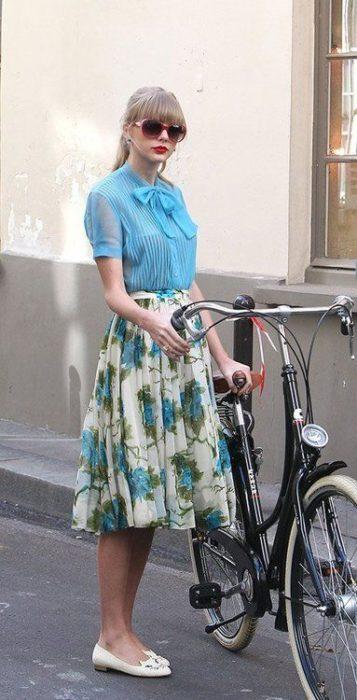 Taylor Swift con falda en estampado floral y blusa azul cielo