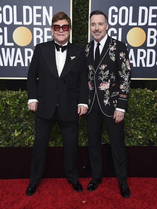 Elton John y David Furnishposando abrazados durante los Globos de Oro 2020