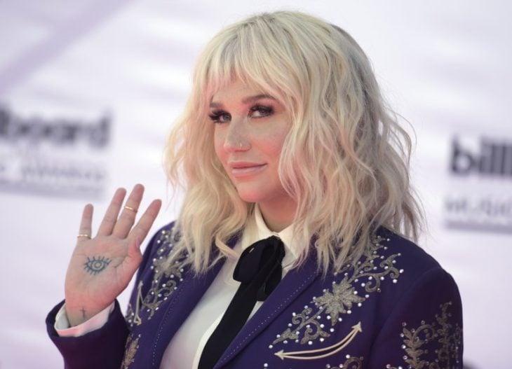 Kesha mostrando uma tatuagem na palma da mão em um tapete vermelho