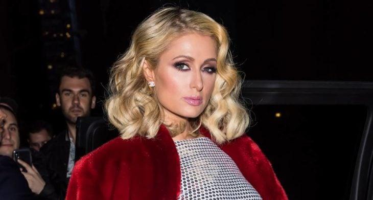 Paris Hilton com casaco vermelho posando para uma selfie