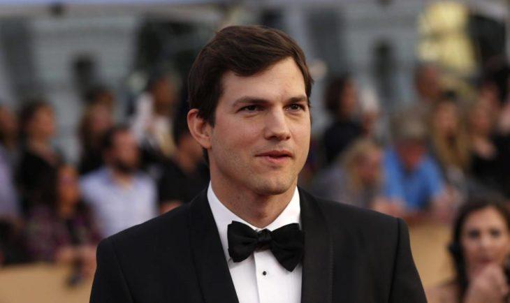 Ashton Kutcher sonriendo ligeramente para una fotografía en una alfombra roja