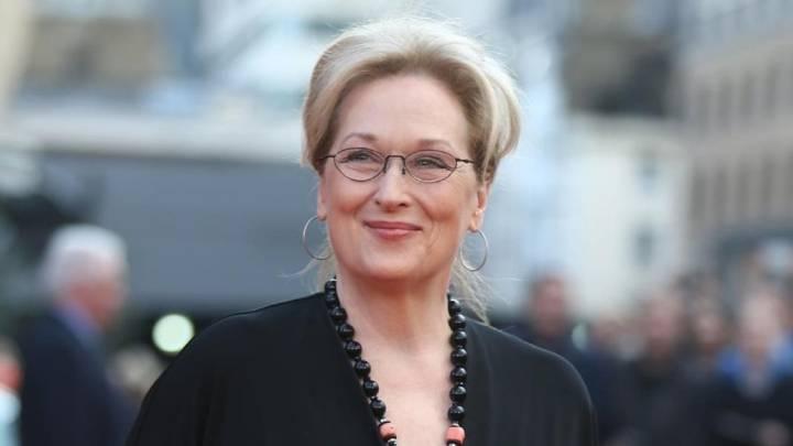 Meryl Streep sorrindo e usando óculos em um tapete vermelho