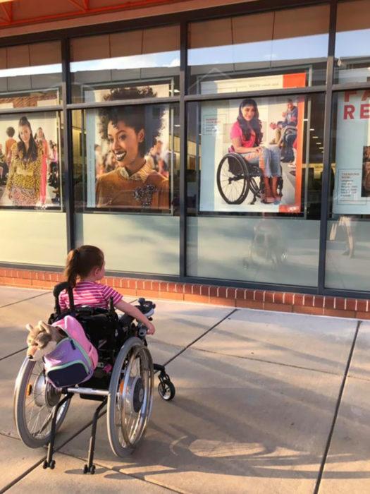Niña en silla de ruedas viendo afiche de película con chica en silla de ruedas