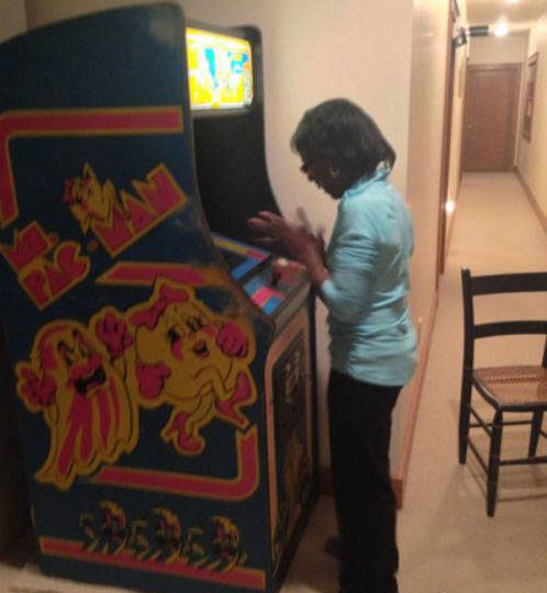 Mujer jugando en máquina de videojuegos arcade
