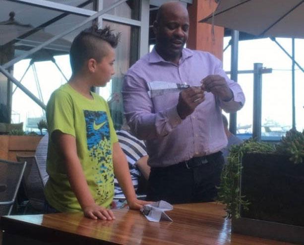 Empleado de restaurante ayuda a un chico a hacer un avión de papel