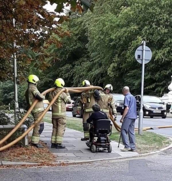 Bomberos ayudando a un hombre en silla de ruedas a cruzar la calle