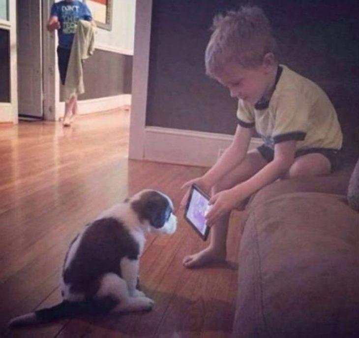 Niño enseñándole tablet a un perrito