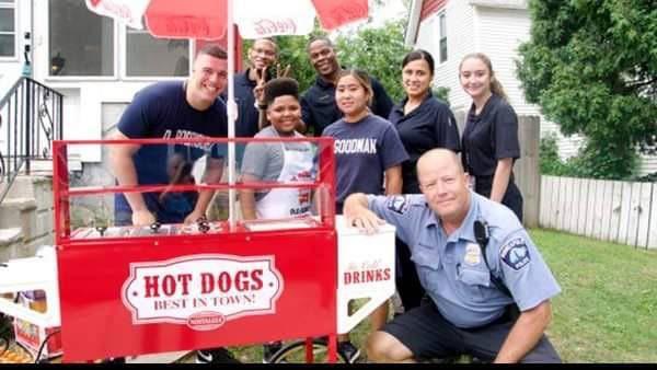 Niño con empleados de salubridad en puesto de hot dogs