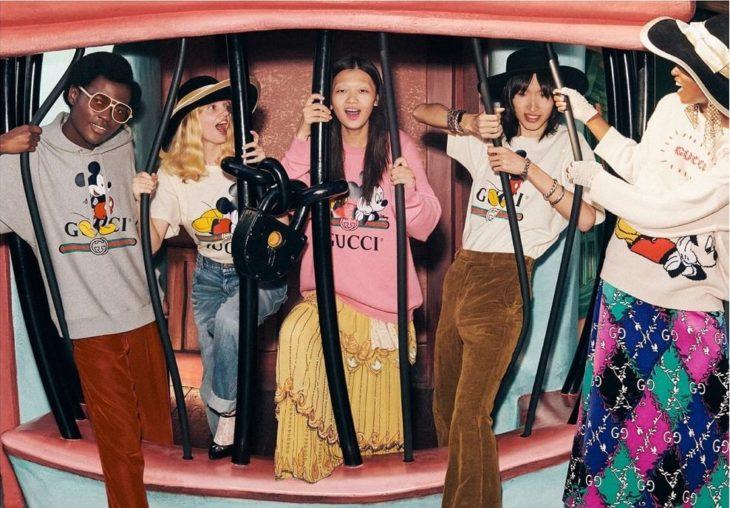 Grupo de amigos tras las rejas y modelando para la colección Gucci x Mickey Mouse