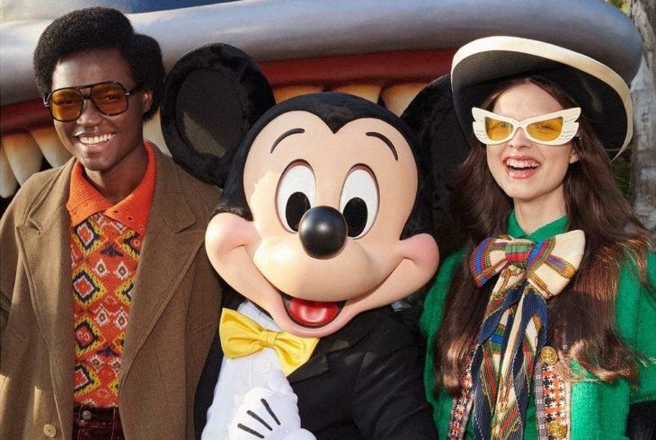 Pareja sonriendo y modelando para la colección Gucci x Mickey Mouse