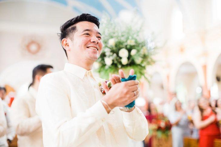 Chico vestido de novio mientras ve a su esposa caminando hacia el altar