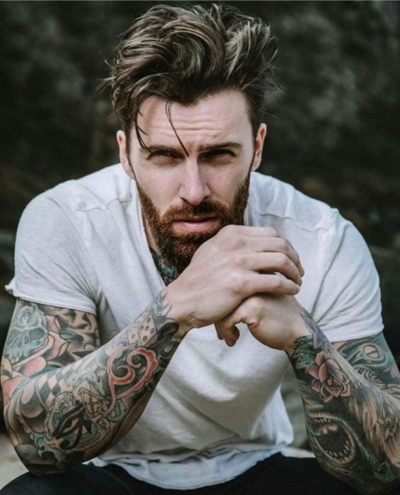 Mujeres prefieren a hombres con barba, tatuados y con panza; guapo chico con los brazos tatuados, barba y cabello corto