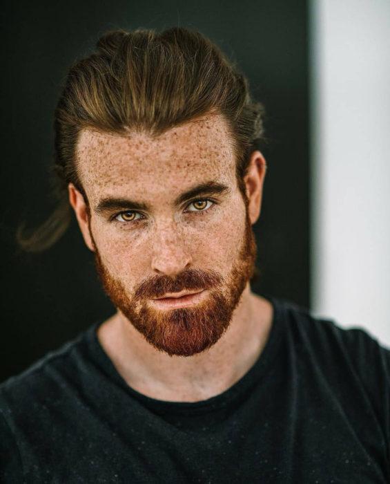 Mujeres prefieren a hombres con barba, tatuados y con panza; chico pelirrojo con pecas, cabello largo peinado en una coleta, ojos miel