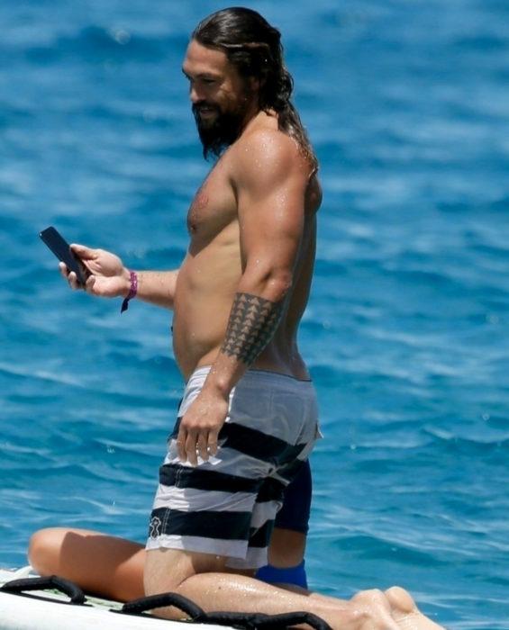 Mujeres prefieren a hombres con barba, tatuados y con panza; Jason Momoa surfeando