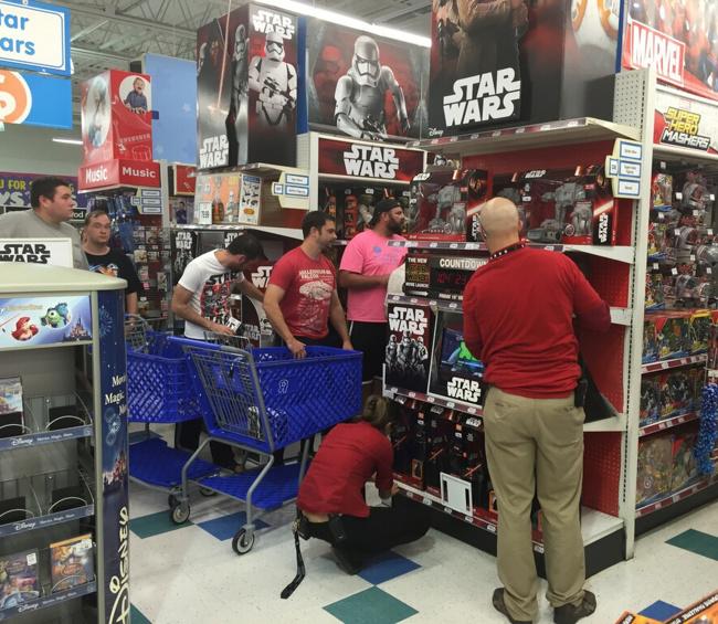 Hombres buscando juguetes en el mueble de Star Wars
