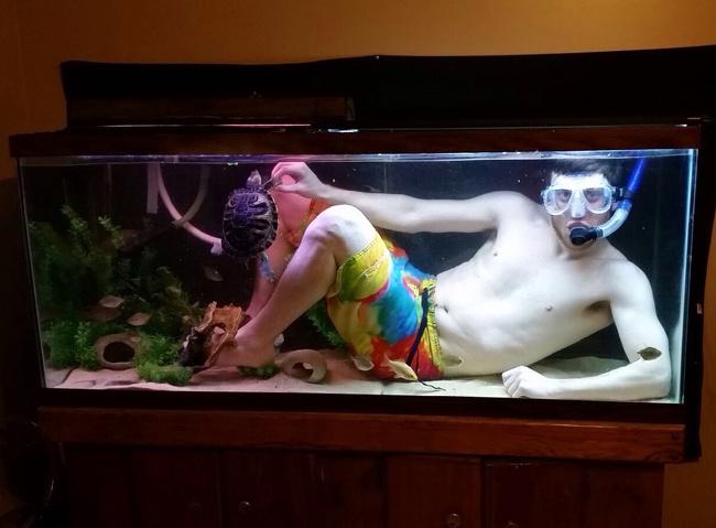 Chico vestido de buzo y dentro de una pecera para tortugas