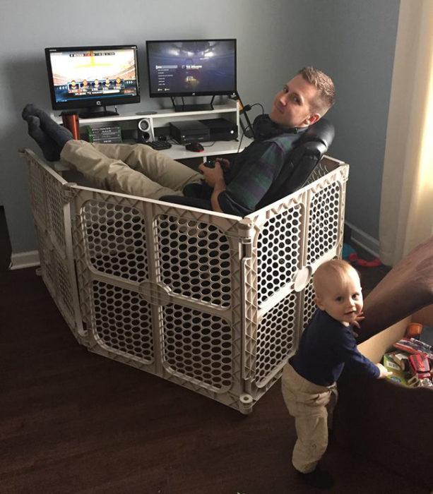 Chico jugando videojuegos y encerrado en un corralito para bebés