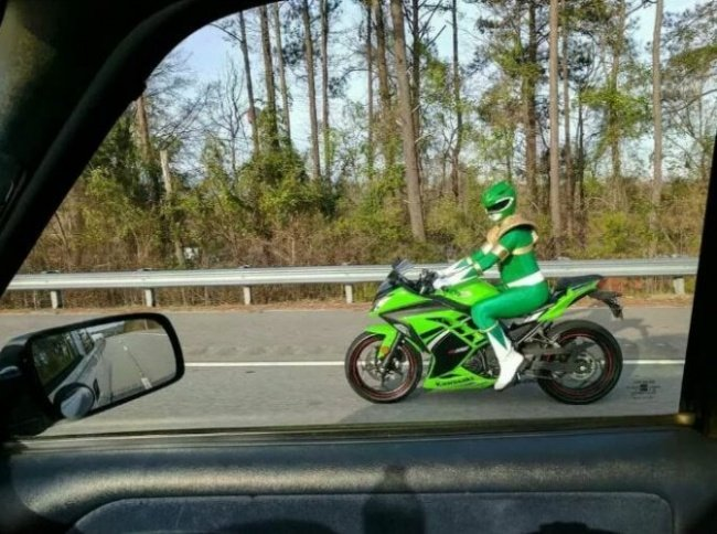 Chico manejando su motocicleta mientras está vestido de Power Ranger