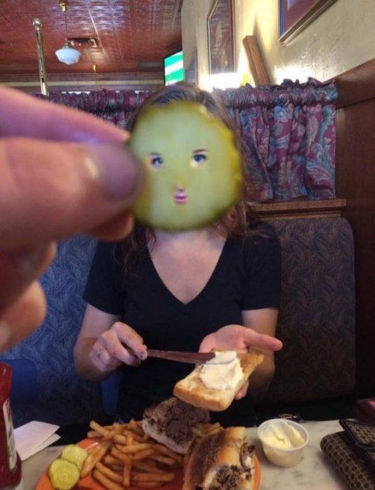 Chico poniendo un pepinillo en el rostro de su novia