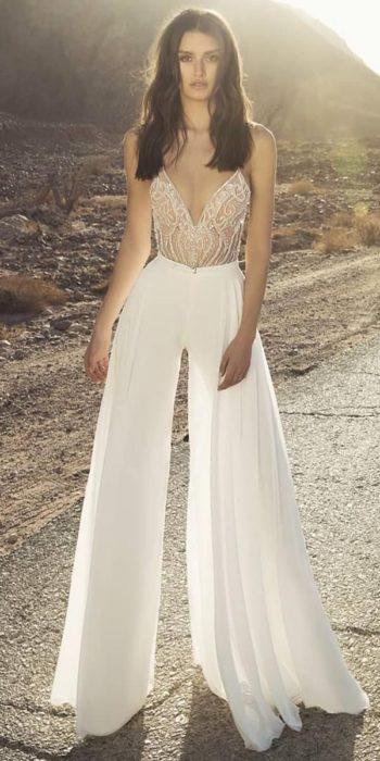 Chica usando un jumpsuit de color blanco con pedrería de cristal en la parte superior