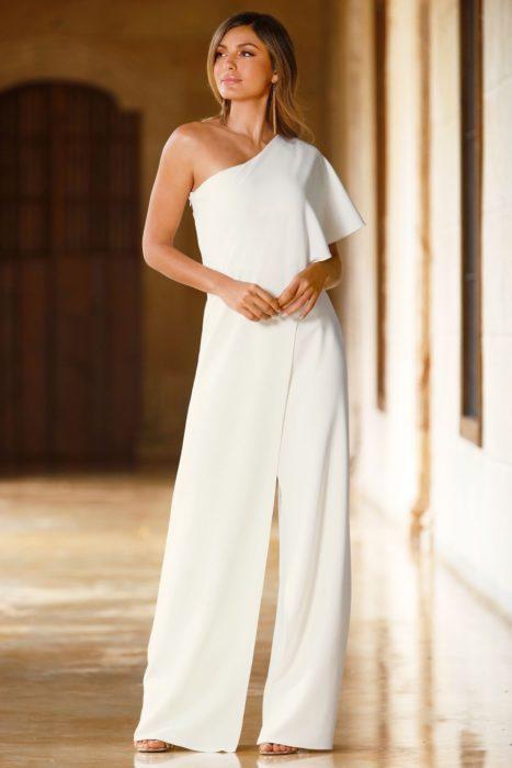 Chica usando un jumpsuit de color blanco con un hombro descubierto