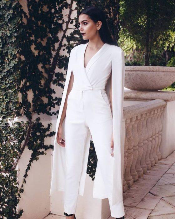 Chica usando un jumpsuit de color blanco con una capa