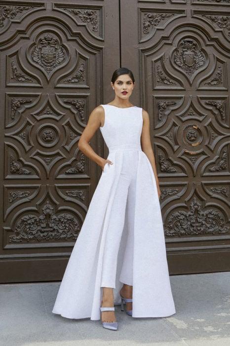 Chica usando un jumpsuit de color blanco con capa a partir de las caderas