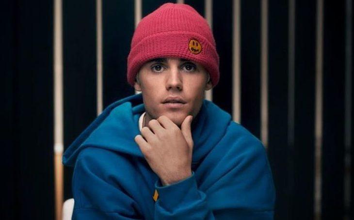 Justi Bieber sentado en una silla modelando su línea de ropa deportiva