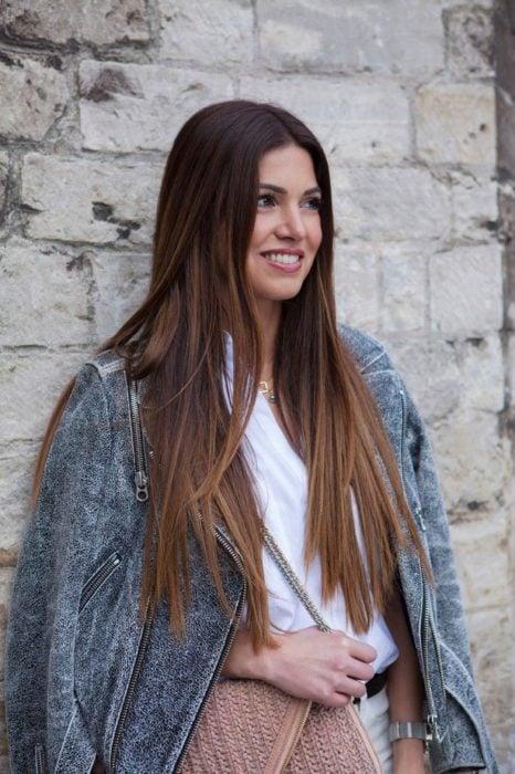 Chica de cabello largo recto usando blusa blanca y americana de mezclilla