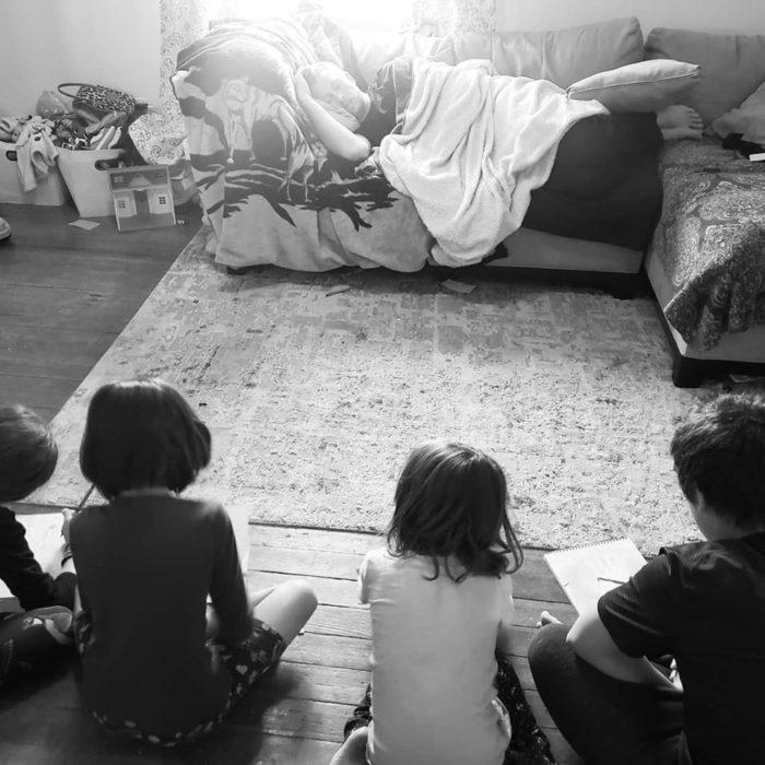 Niños sentados frente a su padre mientras lo dibujan
