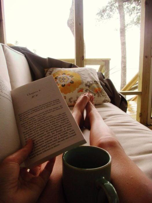 Mujer leyendo, recostada en el sofá, tomando té