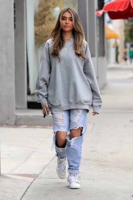 Chica llevando sudadera amplia en tono gris con jeans rotos
