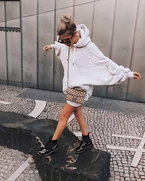 Chica con botas estilo milatr en negro y hoodie amplia en gris