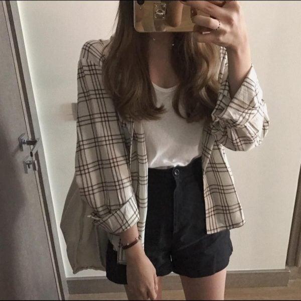 Chica con camisa a cuadros amplia y falda en negro