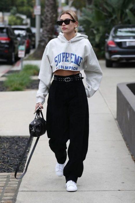 Chica con jeans amplios en tono negro y hoodie gris claro