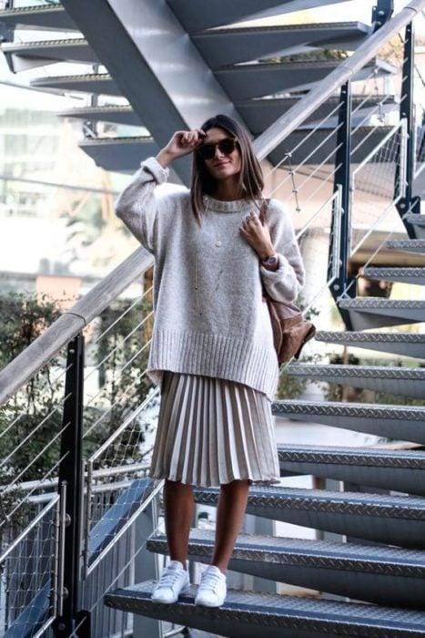 Chica con falda plizada en gris y sudadera del mismo tono