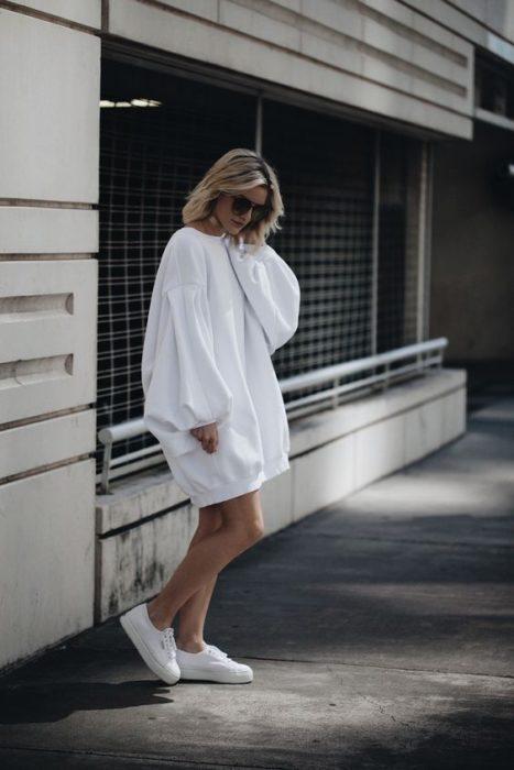 Chica con sudadera en blanco amplia como vestido
