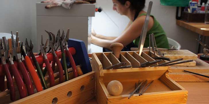 Mujer revisando cajones con material para elaborar joyería