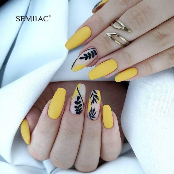 Manicura amarilla con diseño de flores en negro y efecto mate