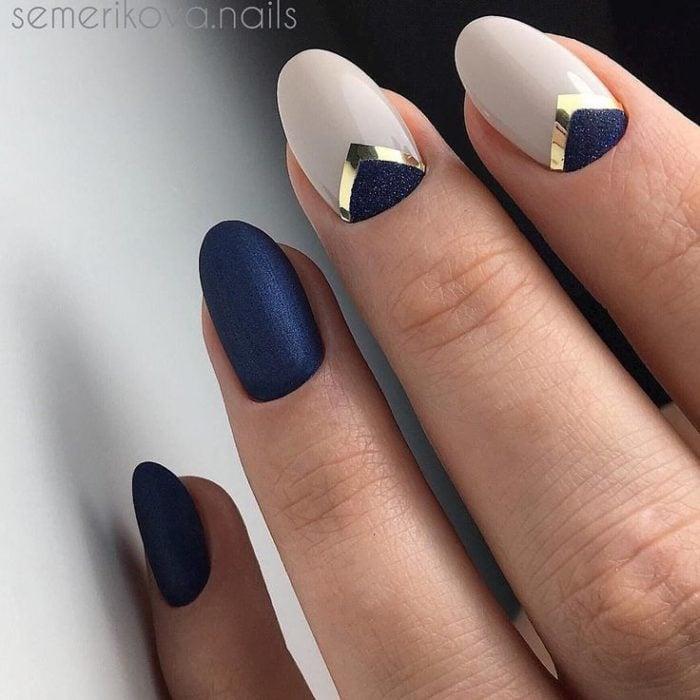 Manicura en tono azul marino y beige con detalles dorados