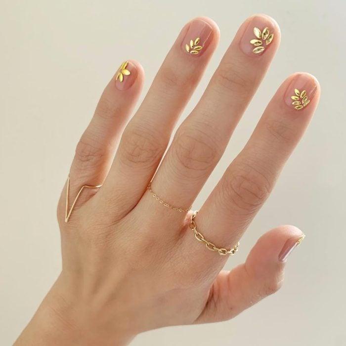 Manicura natural con incrustaciones en tono dorado