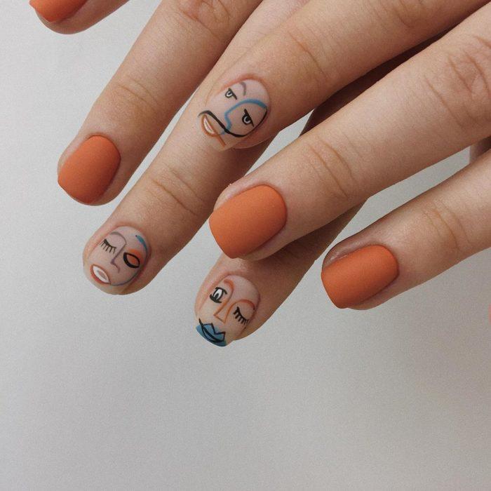 Manicura en tono naranja, con nail art de rostros y efecto mate
