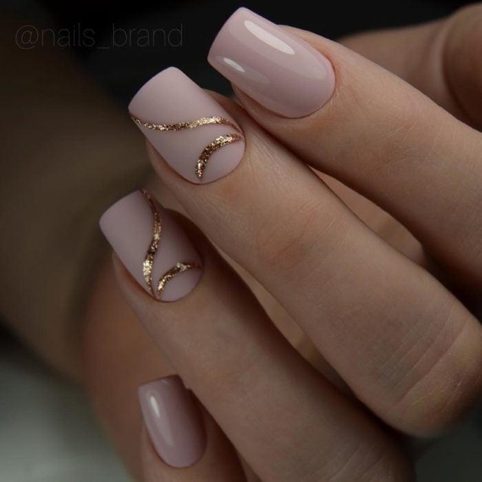 manicura rosa palo en mate con detalles de brillo dorados