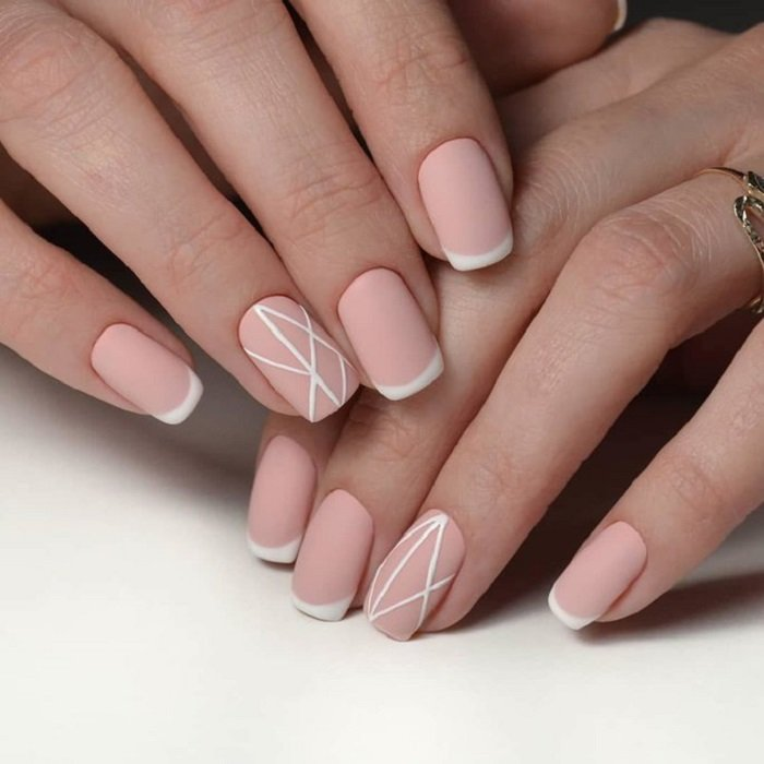 Manicura rosa pastel con detalles en blanco y efecto mate