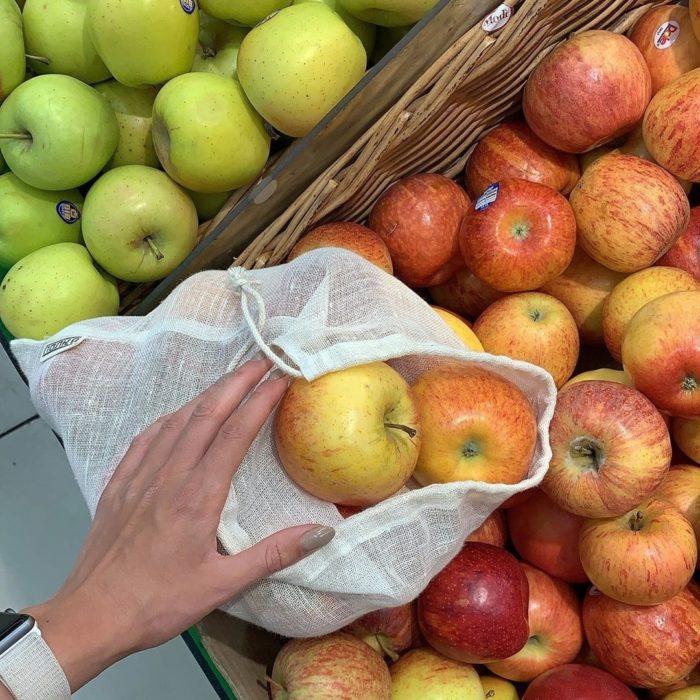 Mano escogiendo manzanas rojas y verdes en canastas de mimbre