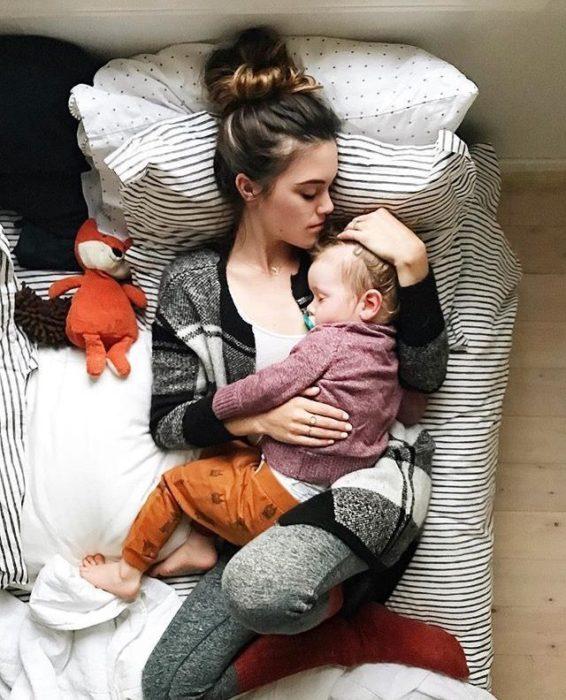 Mujer recostada con bebe en brazos