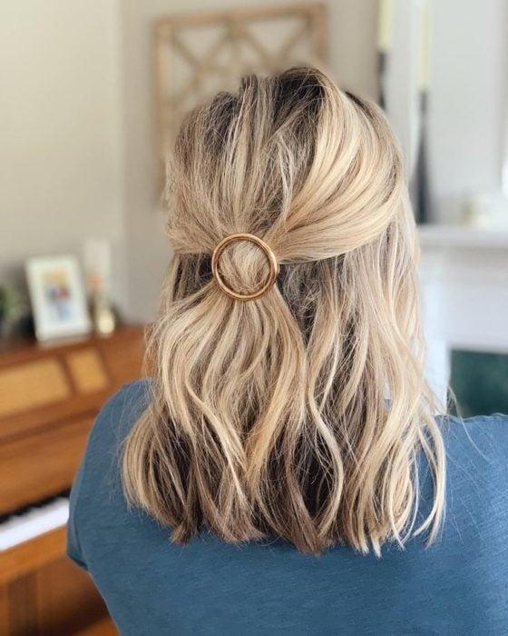 Media cola con broche en cabello corto, ondulado y rubio
