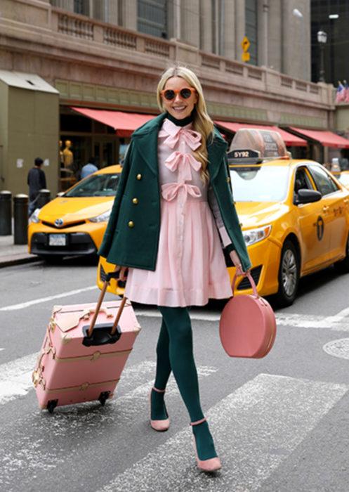 Outfits con medias de colores; mujer con maleta cruzando la calle con taxis detrás, cabello rubio, lentes de sol anaranjados, vestido y zapatos rosas, saco y medias verdes