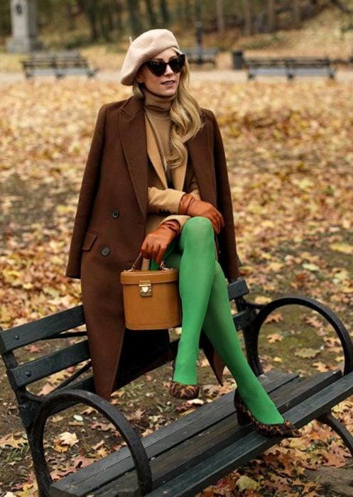 Outfits con medias de colores; mujer sentada en banca de parque, con boina francesa, lentes de sol, saco café, medias verdes, zapatos de animal print