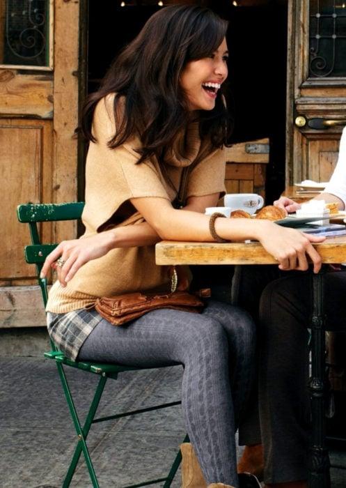 Outfits con medias de colores; mujer riendo mientras bebe un café, medias gruesas grises